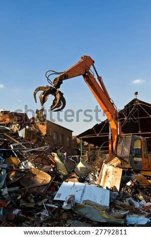 An orange hydraulic excavator with a scrap metal grab attached in the process of dropping metal onto the scrap heap set against a blue sky.