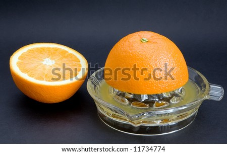 An orange juicer with cut orange. Angled top shot isolated against a black background