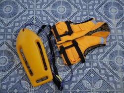 An orange life jacket and an orange plastic rescue torpedo buoy for lifeguard on the pool floor. Compliance with safety rules when swimming