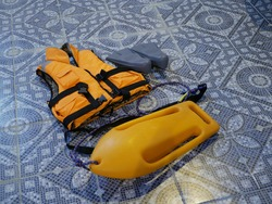 An orange life jacket, gray small rubber flippers, and an orange plastic rescue torpedo buoy for the lifeguard on the pool floor. Compliance with safety rules.