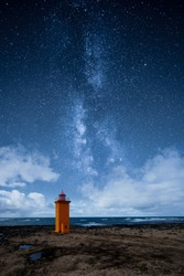 An orange lighthouse by the ocean at night with epic milky way on the sky