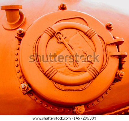 An orange, metallic emblem of an anchor and life ring. A portal hatch with bolts and rivets. A symbol of maritime or nautical endeavors. #1457295383