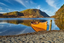 An orange rowboat sits quietly on a lake shore in the Lake District, Cumbria, UK, with the mountains and blue sky in the background. There is no wind, so there is a clear reflection on the water.