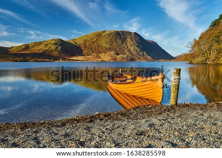 An orange rowboat sits quietly on a lake shore in the Lake District, Cumbria, UK, with the mountains and blue sky in the background. There is no wind, so there is a clear reflection on the water. Stok fotoğraf ©