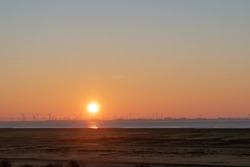 An orange shaded beautiful sunset on a boundless sea in Norderney