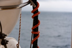 An orange ship rope is tied to a lifeboat with a maritime knot on the railing of a passenger ship - in the background you can see the deep blue sea on a beautiful summer day - concept of rescue