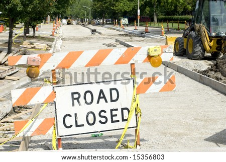 An orange striped 'Road Closed' sign outside a construction zone.