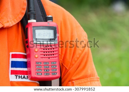 An orange suit of the Fire Rescue unit in Thailand with Thai Flag\'s badges on the chest with the red radio communication devices