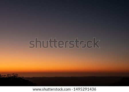 An orange sunrise over the Blue Mountains creates a beautiful silhouette of the foreground #1495291436