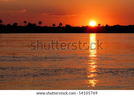 An orange sunset over the Zambezi river in Zambia.  The sun and the reflection create a cool letter 'i'.  The water at the bottom of the frame can easily be cloned out to make the 'i' more obvious.