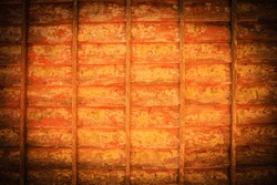 An orange tinted vignette photo of a rustic weathered wooden wall covered with peeling paint.