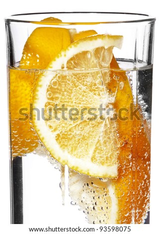 An orange wedge and ice in a glass of soda water. Bubbles are collecting on the surface of the orange wedge.