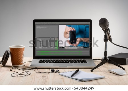 An ordinary workplace of a blogger with a modern laptop and an interface of an application for video editing process. Professional microphone for recording and headphones.