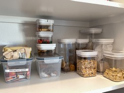 An organized pantry shelf with various types of cookies, cereal and snacks tidily put in plastic containers.