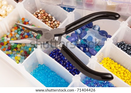 An organizer full of multicolored beads and tools for making jewelry and crafts.