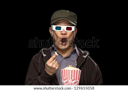 An oriental young man eating pop corn and being scared at a horror movie