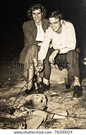 An original photograph of a couple outside cooking over an open fire.