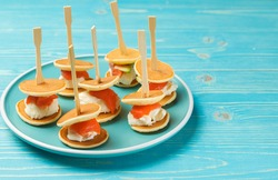 An original snack for parties and receptions. Mini sandwich of pancake, soft cheese and salmon. Dish with mini stickers on a blue wooden background. Horizontal frame, copy of the space