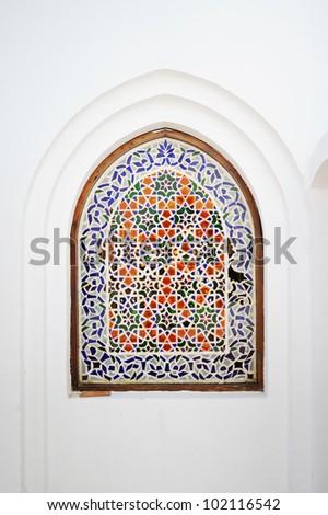 An ornate arch window with flowery islamic motif