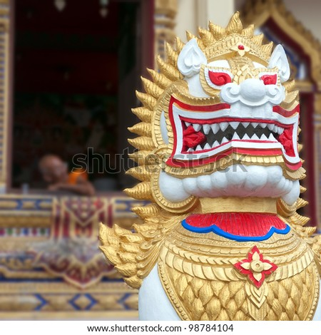 An ornate chinese lion adorns the entrance to a temple in Thailand.