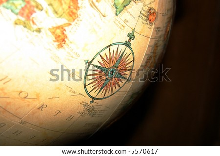 An ornate compass detail illustration on a large spinning globe.