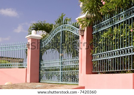 An ornate iron gate and fence at the entrance to a luxury Caribbean estate.