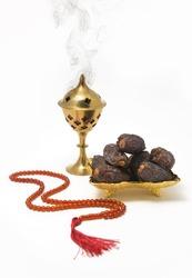 An Oudh burner, dates and islamic prayer beads