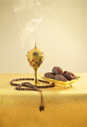 An oudh burner, islamic prayer beads and dates on golden background