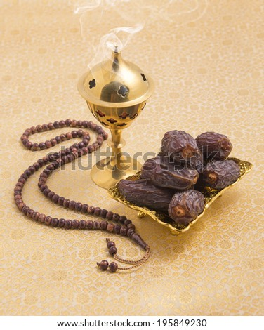 An oudh burner prayer beads and dates