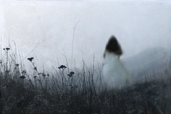 An out of focus, blurred ghostly woman wearing a white dress, running away from the camera. On a misty winters day in the countryside. With an artistic, textured, edit.