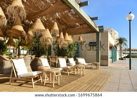An outdoor cafe on the promenade. Eco-friendly design using natural materials. Wooden canopy with wicker nets and conical straw lampshades and rattan and wood furniture.  Alicante. Spain.
