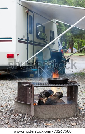 An outdoor grill at a Pennsylvania State Park with a camping trailer in the background.