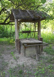 An outdoor old-fashioned, old hand made water well with a wooden roof in the garden. Restoring an old water well.