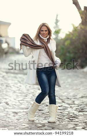 An outdoor portrait of a beautiful long-haired blond young woman wearing a white coat, skinny jeans and white boots, walking down the street and smiling on a cold winter day. Shallow depth of field. - stock photo
