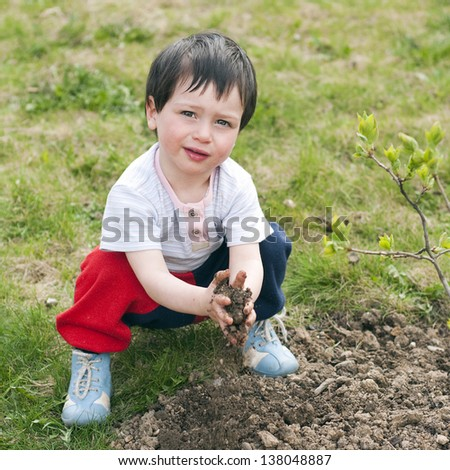 An outdoor portrait of a cute child playing with earth soil in a garden.
