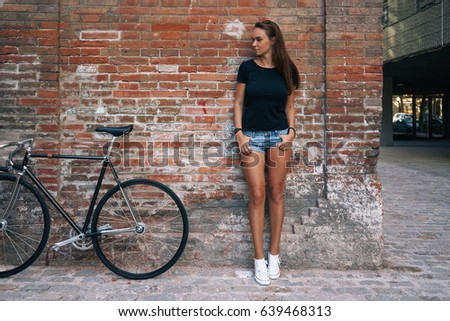 An outdoor portrait of a young cute student girl wearing black blank t-shirt and blue jeans shorts with a fixed gear bicycle while standing on the brick wall background. Empty space for text or design #639468313