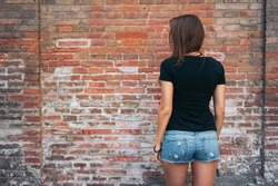 An outdoor portrait of a young pretty hipster girl with long dark hair wearing black blank t-shirt and blue jeans shorts standing with her back to the camera on the brick wall background.