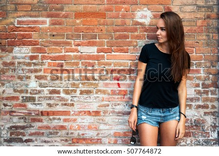 An outdoor portrait of a young pretty hipster girl with long dark hair wearing black blank t-shirt and blue jeans shorts standing on the brick wall background. #507764872