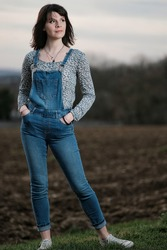 An outdoor portrait of a young woman wearing dungarees in the countryside