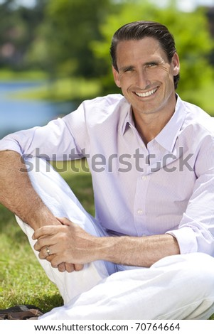 An outdoor portrait of handsome middle aged man sitting down, shot with sunlight against a natural green background - stock photo