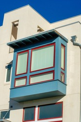 An outlaying closed balcony with windows on a white building