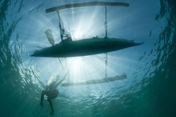An outrigger canoe is silhouetted by bright sunlight in North Sulawesi, Indonesia. Millions of people make their living by utilizing marine resources.