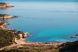 An outrigger canoe sits in a translucent turquoise bay off the coast of La Revellata near Calvi in the Balagne region of Corsica under a clear blue sky