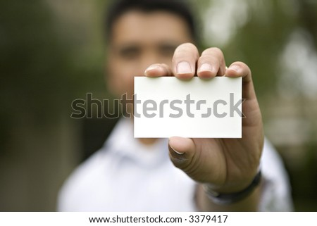 An outside shot of a Businessman holding out a Blank Business Card