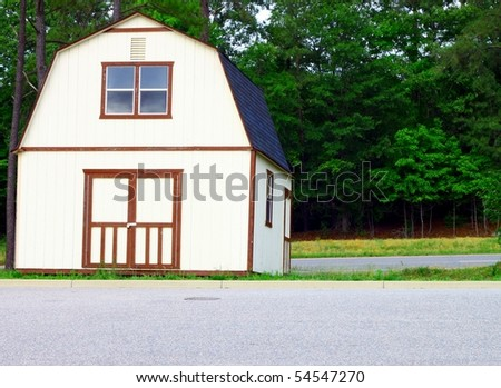 an outside storage building slopping down the embankment  toward the road