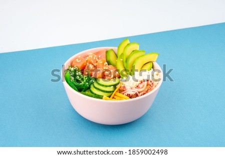 An overhead diagonal, isometric projection photo of poke bowl, traditional Hawaiian and Japanise raw fish salad, from seaweed, rice, salmon, cucumber, soy sause and avocado. with chopsticks and sesame