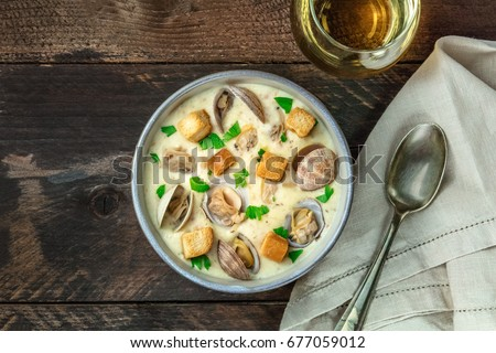 An overhead photo of a bowl of clam chowder, decorated with fresh parsley and croutons, on a dark rustic texture with a spoon, a glass of white wine, and a place for text