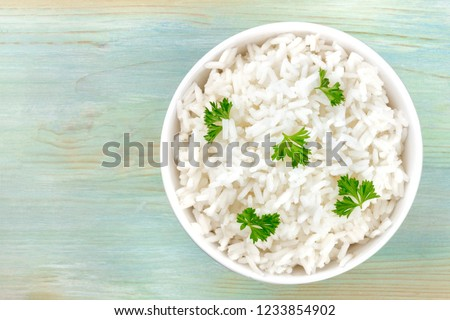 An overhead photo of a bowl of cooked white long grain rice, shot from above on a teal blue background with a place for text