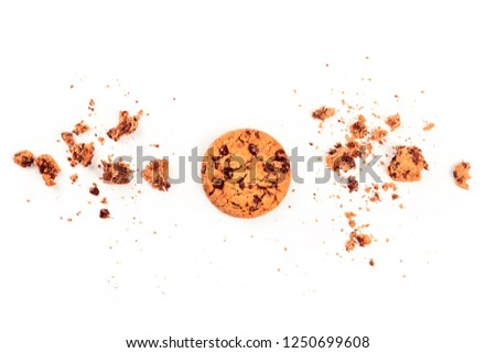 An overhead photo of a freshly baked golden brown chocolate chip cookie, shot from above on a white background with crumbs and copy space #1250699608