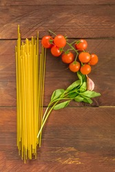 An overhead photo of a letter P for pasta, formed by spaghetti, cherry tomatoes, a garlic clove, and a sprig of basil leaves, on a dark wooden background texture with copy space
